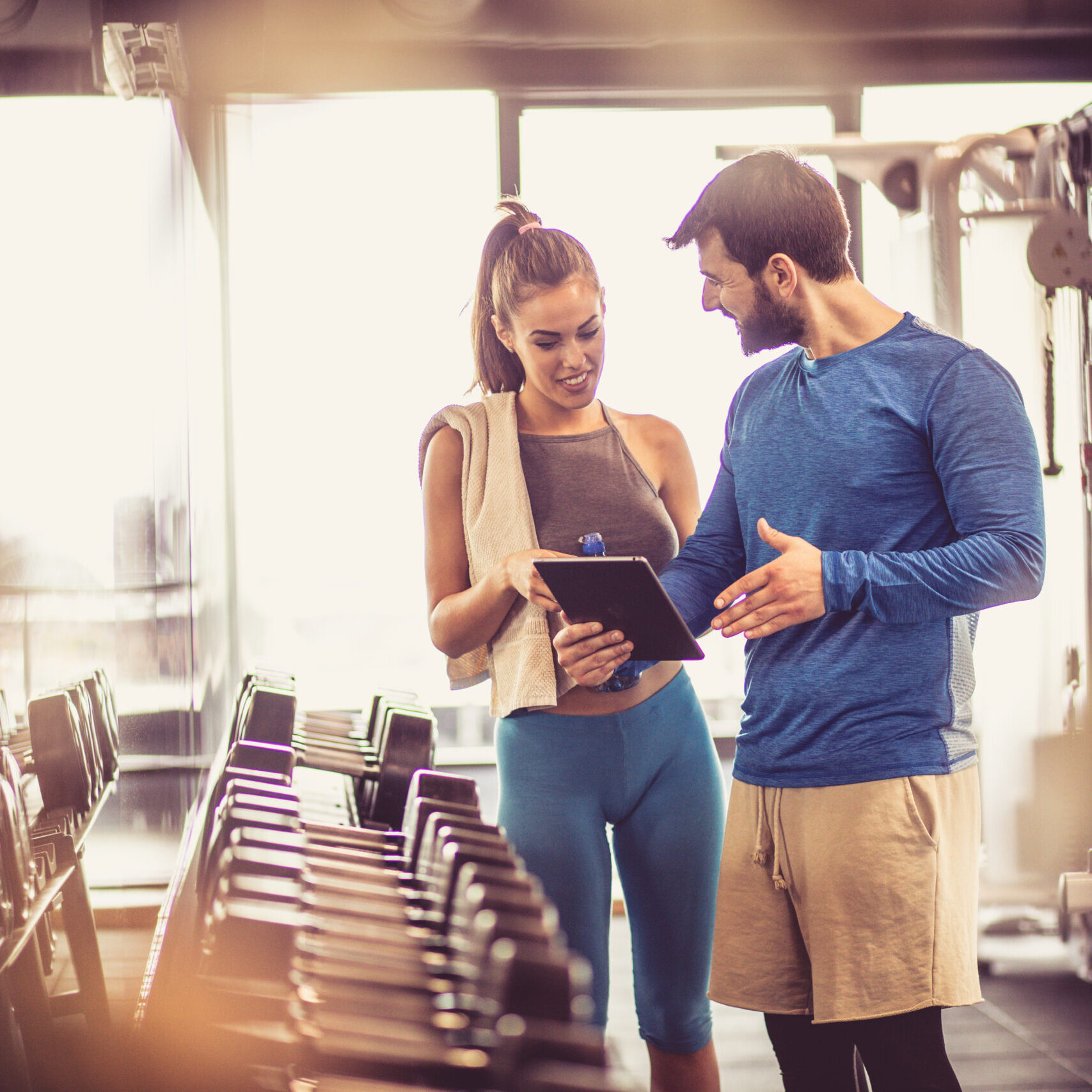 Young woman discussing workout progress with fitness instructor.